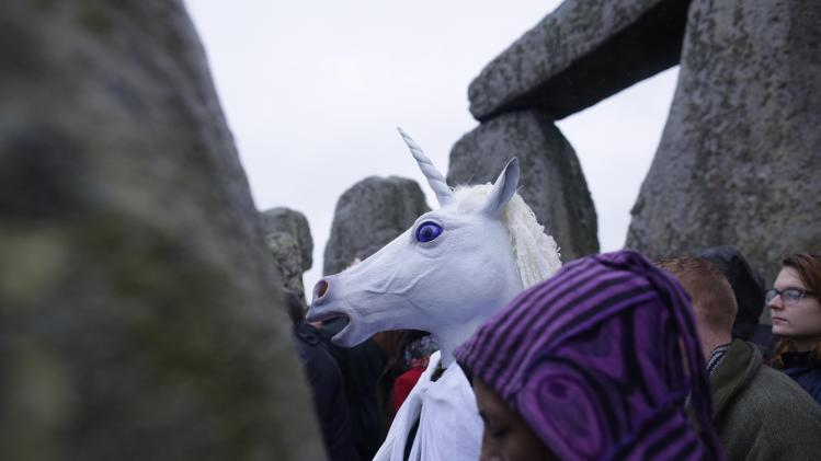 A reveller wearing a unicorn mask celebrates the winter solstice at Stonehenge in Amesbury, southern England