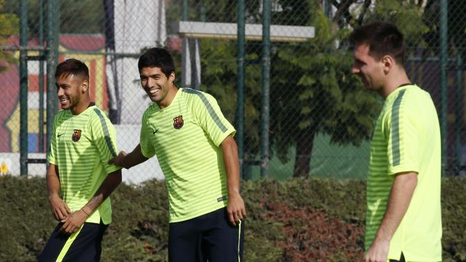 Barcelona's players Neymar and Luis Suarez joke next to Lionel Messi during a training session at Joan Gamper training camp