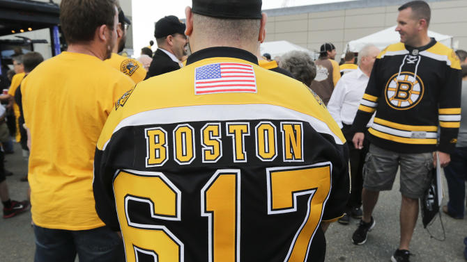 """A fan wears a Boston Bruins jersey bearing the Boston area code and """"Boston Strong,"""" remembering the city's solidarity after the Boston Marathon bombing in April, before Game 4 of the NHL hockey Stanley Cup Finals between the Bruins and the Chicago Blackhawks, Wednesday, June 19, 2013, in Boston. (AP Photo/Charles Krupa)"""