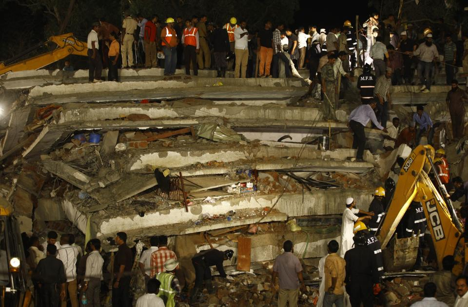 Rescue workers look for trapped people after a residential building collapsed in Thane, Mumbai, India, Thursday, April 4, 2013. At least 6 persons were killed and 40 were injured when an under construction residential building collapsed on Thursday evening according to local reports.(AP Photo/Rafiq Maqbool)