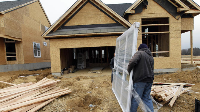 In this Feb. 8, 2012 photo, two workers carry a window for a home  under construction in a new subdivision by Toll Brothers, in Yardley, Pa.   Toll Brothers says its fiscal fourth-quarter net income in 2012 soared, helped by a large income tax benefit and a 48 percent rise in revenue. The luxury homebuilder delivered more homes and its order backlog increased. (AP Photo/Alex Brandon)