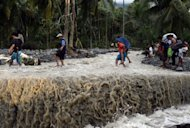 Residents cross a road destroyed by Typhoon Bopha in the village of Andap, New Bataan town on December 5. Manila has appealed for international assistance after a deadly typhoon killed 477 people left a quarter of a million homeless