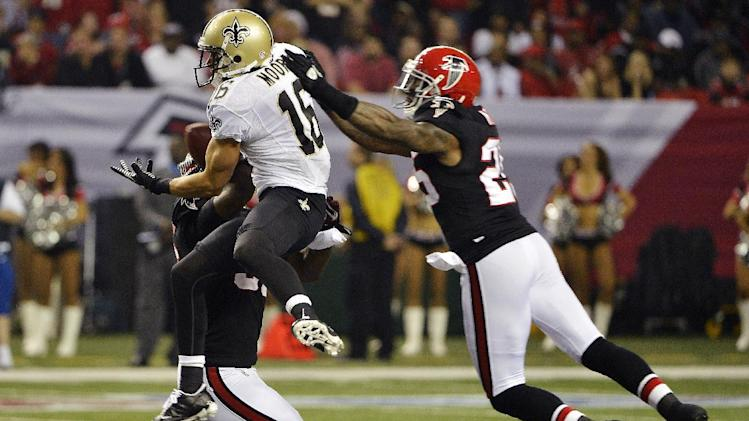 New Orleans Saints wide receiver Lance Moore (16) makes a catch between Atlanta Falcons' Sean Weatherspoon, obscured, and Charles Mitchell (26) during the first half of an NFL football game, Thursday, Nov. 29, 2012, in Atlanta. (AP Photo/Rich Addicks)