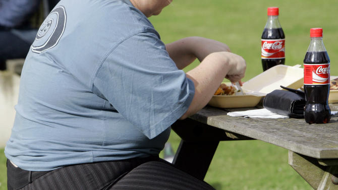 FILE - In this Oct. 17, 2007 file photo, an overweight person eats in London. Nearly everywhere around the world, people are living longer and fewer children are dying. But more and more the world is grappling with the diseases and disabilities of modern life, according to the most expansive global look so far at life expectancy and the biggest health threats nation by nation. (AP Photo/Kirsty Wigglesworth)