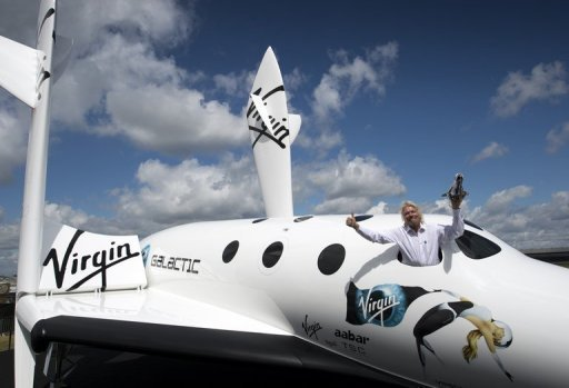 <p>British billionaire Richard Branson in the window of a replica of the spaceship he plans to launch for his new Virgin Galactic space tourism programme, at the Farnborough Air Show in Britain. Branson said Wednesday that he and his family will be the first on board his new Virgin Galactic space tourism programme.</p>