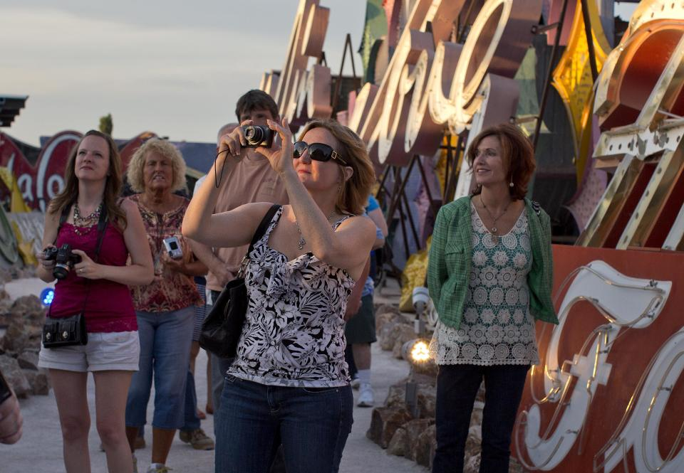Tourists walk through a display of old hotel and casino signs at sunset at the Neon Museum in Las Vegas on Friday, May 24, 2013. For the past six months, tourists have had to squint up at the hulking metal forms through the desert sun. On Friday, the Neon Museum unveiled nighttime hours. (AP Photo/Julie Jacobson)