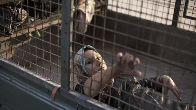 A wounded Syrian woman arrives at Dar El Shifa hospital in Aleppo, Syria, Wednesday, Oct. 3, 2012.   Three suicide bombers detonated cars packed with explosives in a government-controlled area of the battleground Syrian city of Aleppo on Wednesday, killing at least 34 people, leveling buildings and trapping survivors under the rubble, state TV said. More than 120 people were injured, the government said. (AP Photo / Manu Brabo)