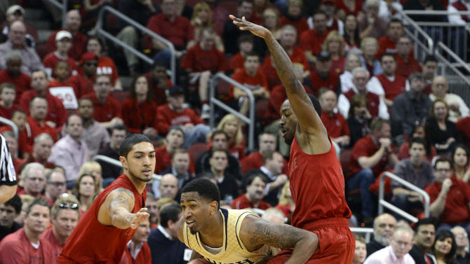 Notre Dame's Eric Atkins, center, fights his way through the defense of Louisville's Peyton Siva, left, and Russ Smoth during the first half of an NCAA college basketball game Saturday March 9, 2013 in Louisville, Ky. (AP Photo/Timothy D. Easley)