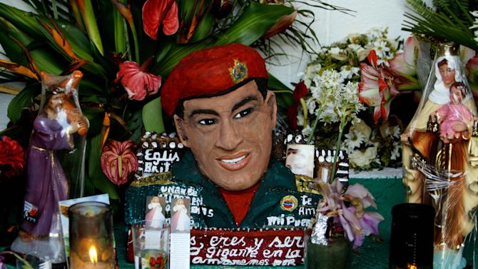 """A bust of late Venezuela's President Hugo Chavez is adorned with flowers, candles and religious images inside a people's shrine built in his honor at the """"23 de Enero"""" or """"23rd of January"""" slum in Caracas, Venezuela, Wednesday, April 3, 2013. The shrine, named  """"Saint Hugo Chavez del 23"""", has been visited by tens of thousands of Venezuelans to pay homage to a president for some, a saint for others. (AP Photo/Fernando Llano)"""