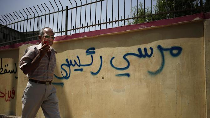 """An Egyptian man walks by a graffiti in Arabic that reads, """"Morsi my president"""", referring to the ousted Egyptian President Mohammed Morsi, in Cairo, Egypt, Sunday, Sept. 8, 2013. An Egyptian military official says helicopter gunships have launched new strikes targeting militant hideouts in the northern Sinai peninsula, on a second day of a major offensive aiming at quelling an insurgency in the lawless region. (AP Photo/Hassan Ammar)"""
