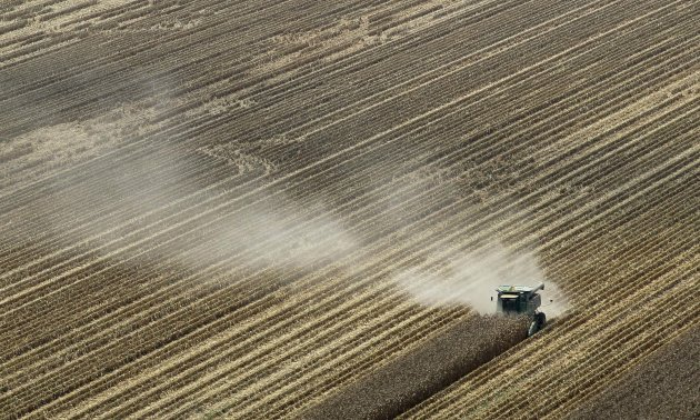 FILE - In this Aug. 16, 2012 file photo, dust is blown from behind a combine harvesting corn in a field near Coy, Ark. The remnants of Tropical Storm Isaac could ease but not eliminate drought conditions in Arkansas, Missouri and Illinois by dropping 2 to 5 inches of rain. (AP Photo/Danny Johnston, File)