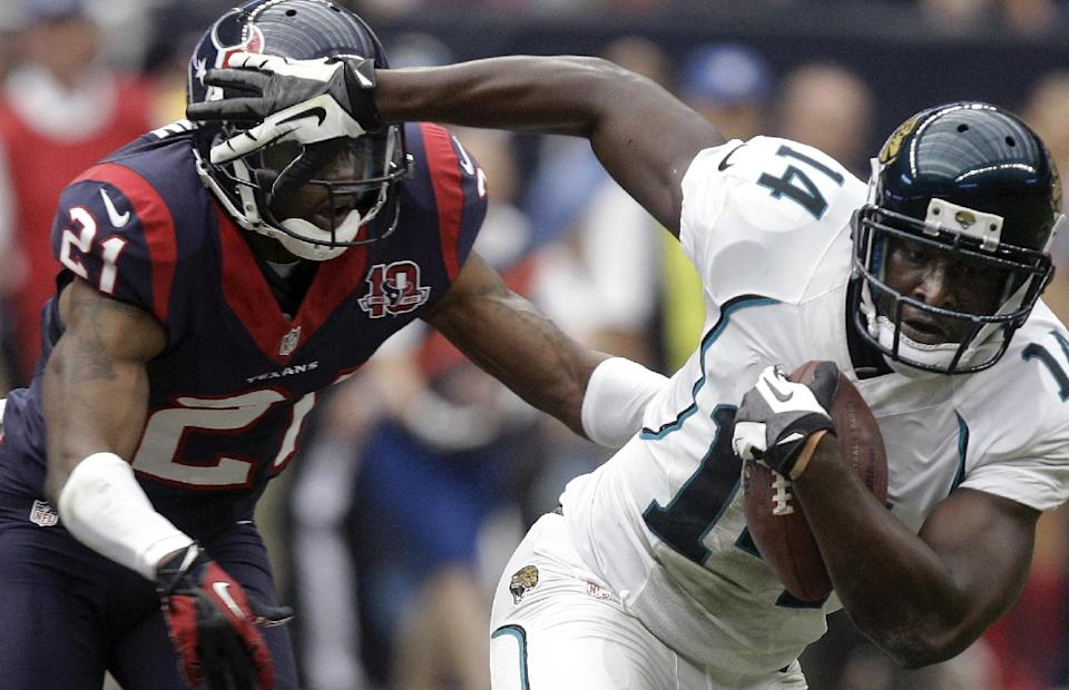 Jacksonville Jaguars wide receiver Justin Blackmon (14) breaks away from Houston Texans' Brice McCain (21) to score a touchdown during the fourth quarter of an NFL football game on Sunday, Nov. 18, 2012, in Houston. (AP Photo/Patric Schneider)