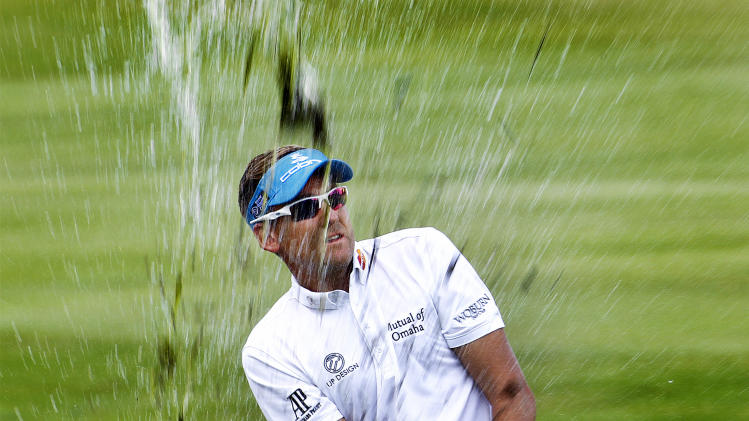 Ian Poulter, of England, sprays water and mud after hitting out of the water hazard on to the 12th green during the second round of the St. Jude Classic golf tournament at TPC Southwind on Friday afternoon, June 7, 2013, near Memphis, Tenn. Poulter bogeyed the hole. (AP Photo/The Commercial Appeal, Mark Weber)