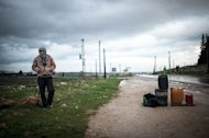 A Syrian man stands next to gas cans at a make-shift gas station on the road to Aleppo, in February 16, 2013