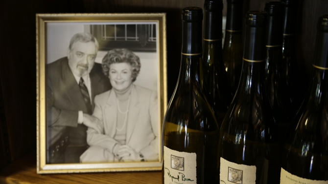 "In this photo taken Thursday, April 11, 2013 bottles of Chardonnay are shown beside of photograph of the late actor Raymond Burr and actress Barbara Hale at Raymond Burr Vineyards in Healdsburg Calif. The star of TV's ""Perry Mason"" and ""Ironside,"" also had a passion for wine, which is still celebrated at this small winery in Sonoma County's Dry Creek Valley. (AP Photo/Eric Risberg)"