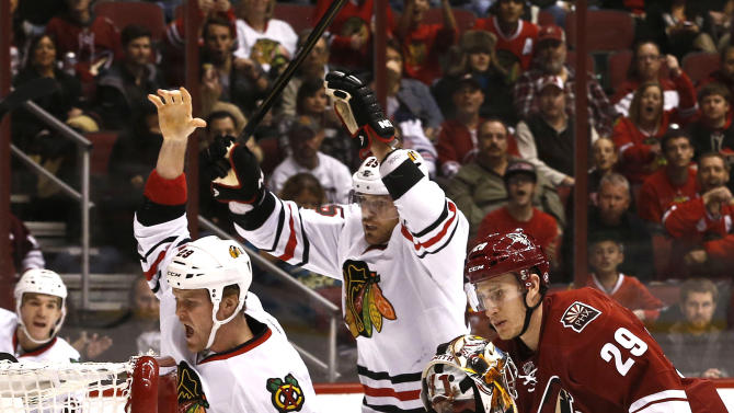 Chicago Blackhawks' Bryan Bickell (29) celebrates goal by teammate Viktor Stalberg (25), of Sweden, as Phoenix Coyotes' Mike Smith (41) and Michael Stone (29) look on during the first period in an NHL hockey game Thursday, Feb. 7, 2013, in Glendale, Ariz.(AP Photo/Ross D. Franklin)