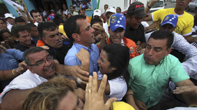 In this Sept. 1, 2012 photo, opposition presidential candidate Henrique Capriles, center left, is embraced by a female supporter during a campaign rally in Miranda, Venezuela.  Capriles and Venezuela's President Hugo Chavez are waging intense, contrasting campaigns ahead of Venezuela's Oct. 7 election while aiming for swing voters among young Venezuelans under 30, middle-class households and women of all social classes. (AP Photo/Fernando Llano)