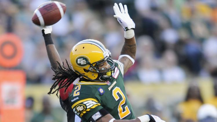 Eskimos' Stamps and RedBlacks Thompson battle for pass during their CFL football game in Edmonton