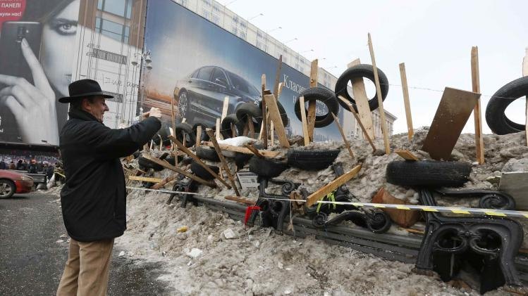 A tourist takes pictures of a barricade erected by Pro-European integration protestors in Independence Square in Kiev