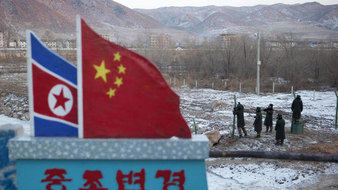 """FILE - In this Dec. 8, 2012 file photo, Chinese paramilitary policemen build a fence near a concrete marker depicting the North Korean and Chinese national flags with the words """"China North Korea Border"""" at a crossing in the Chinese border town of Tumen in eastern China's Jilin province. China is trying to punish ally North Korea for its nuclear and missile tests, stepping up inspections of North Korean-bound cargo in a calibrated effort to send a message of Chinese pique without further provoking a testy Pyongyang government. (AP Photo/Ng Han Guan, File)"""