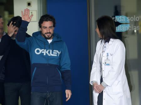McLaren's Formula One driver Fernando Alonso of Spain waves to the media as he leaves the hospital where he was hospitalized since Sunday in Sant Cugat