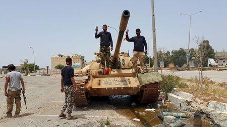 Members of the Libyan pro-government forces gesture as they stand on a tank in Benghazi