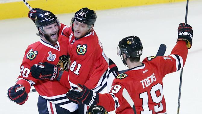 Chicago Blackhawks left wing Brandon Saad (20) celebrates with right wing Marian Hossa (81) and center Jonathan Toews (19) after scoring a goal during the second period of Game 1 in their NHL Stanley Cup Final hockey series against the Boston Bruins, Wednesday, June 12, 2013, in Chicago. (AP Photo/Charles Rex Arbogast)