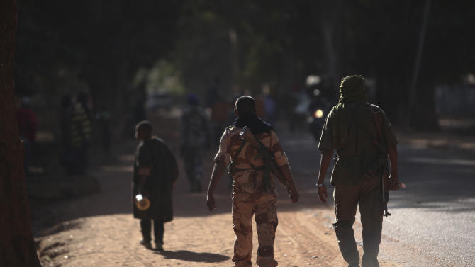 Malian soldiers patrols in a street of Niono, Mali, some 270 kms (180 miles) north of Bamako, Friday, Jan. 18, 2013.  French troops encircled a key Malian town on Friday to stop radical Islamists from striking closer to the capital, a French official said. The move to surround Diabaly came as French and Malian authorities said they had retaken Konna, the central city whose capture prompted the French military intervention last week. (AP Photo/Thibault Camus)