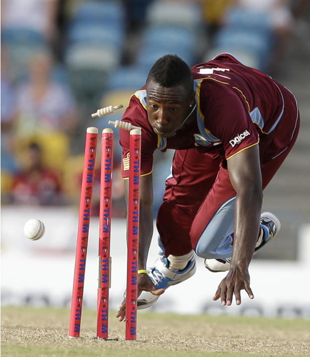 West Indies' Andre Russell aims to run out England's James Tredwell during their first T20 International cricket match at the Kensington Oval in Bridgetown, Barbados, Sunday, March 9, 2014. (A