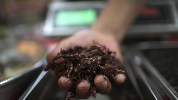 A vendor holds grasshoppers at the San Juan food market in Mexico City