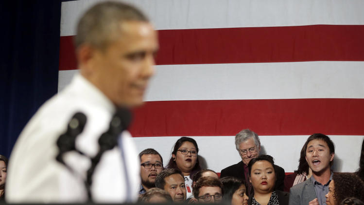 In this Nov. 25, 2013, photo, President Barack Obama, left, stops his speech and turns around in response to an unidentified man, right, who heckled him about anti-deportation policies, at the Betty Ann Ong Chinese Recreation Center in San Francisco. Obama stopped his speech about immigration reform to let this man, who was located directly behind Obama, speak and would respond to his questions. Advocates are frustrated with the failure of House Republicans to tackle immigration. Increasingly, they're focus is on President Barack Obama. The outside groups are demanding that Obama use his powers as chief executive to stop deportations or provide some relief to many of the 11 million immigrants living here illegally. (AP Photo/Pablo Martinez Monsivais, File)