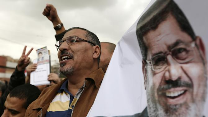 Supporters of Egyptian President Mohammed Morsi, pictured at right, chant slogans during a demonstration outside the presidential palace, in Cairo, Egypt, Wednesday, Dec. 5, 2012. Supporters of Morsi and opponents clashed outside the presidential palace. Wednesday's clashes began when thousands of Islamist supporters of Morsi descended on the area around the palace where some 300 of his opponents were staging a sit-in.(AP Photo/Hassan Ammar)