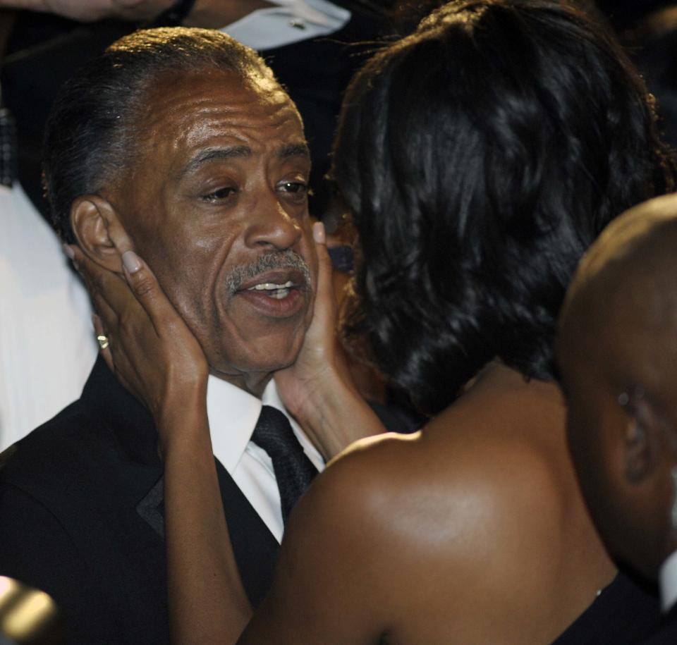 First lady Michelle Obama, right, clasps the face of Rev. Al Sharpton, president, National Action Network, as she greets people after addressing the Congressional Black Caucus Foundation's 42nd Annual Phoenix Awards dinner in Washington, Saturday, Sept. 22, 2012. (AP Photo/Cliff Owen)