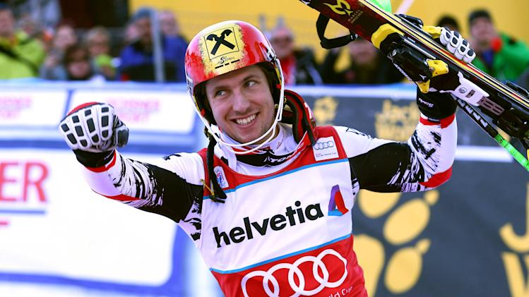 Austria's Marcel Hirscher celebrates at the finish area after winning an alpine ski World Cup men's slalom, looks up from on the podium in Adelboden, Switzerland, Sunday, Jan. 12, 2014. (AP Photo/Giovanni Auletta)