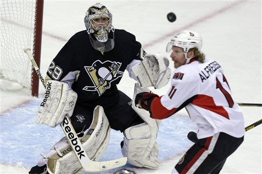 Pittsburgh Penguins goalie Marc-Andre Fleury (29) watches the puck after a rebound, next to Ottawa Senators right wing Daniel Alfredsson (11) during the first period of an NHL hockey game in Pittsburgh on Wednesday, Feb. 13, 2013. (AP Photo/Gene J. Puskar)