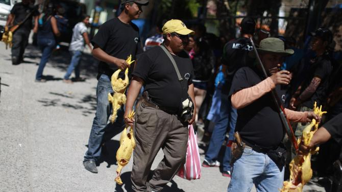 Members of the Community Police of the FUSDEG carry chickens for their lunch in the downtown of the village of Petaquillas