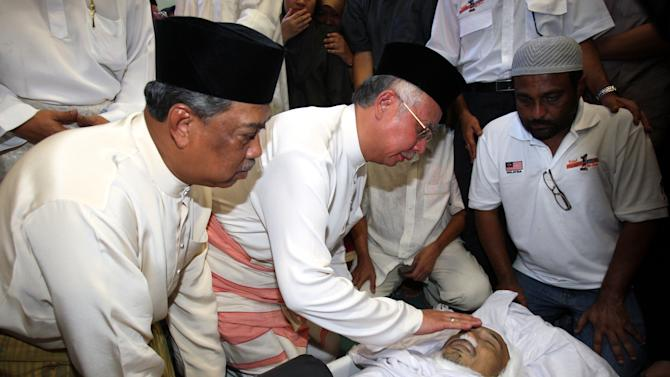 Malaysian Prime Minister, second from left, and his deputy Muhyiddin Yassin, left, pay their last respects to late Bernama TV cameraman Noramfaizul Mohd Nor during a funeral at a mosque at Royal Malaysian Air Force base in Subang, near Kuala Lumpur, Malaysia, Sunday, Sept. 4, 2011. A statement on Bernama's website said 41-year-old Nor was killed Friday, Sept. 2, 2011 in Mogadishu as he accompanied the aid agency Putera 1Malasyai Club on a humanitarian mission. (AP Photo/Lai Seng Sin)