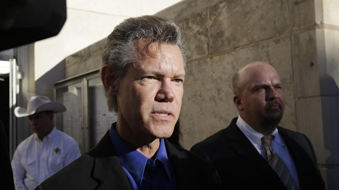 FILE - In this Thursday, Jan. 13, 2013 file photo, entertainer Randy Travis, center, makes comments after exiting the Grayson County Courthouse in Sherman, Texas. Country music star Randy Travis is out of the hospital three weeks after he was admitted with congestive heart failure and later suffered a stroke, Wednesday, July 31, 2013. (AP Photo/Tony Gutierrez, File)