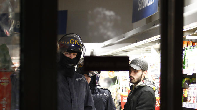 A riot policeman holds a looter in a Sainsbury's supermarket on Deansgate during civil disturbances in Manchester, England, Tuesday, Aug. 9 2011. Britain began flooding London's streets with 16,000 police officers Tuesday, nearly tripling their presence as the nation feared its worst rioting in a generation would stretch into a fourth night. The violence has turned buildings into burnt out carcasses, triggered massive looting and spread to other U.K. cities.  (AP Photo/Jon Super).