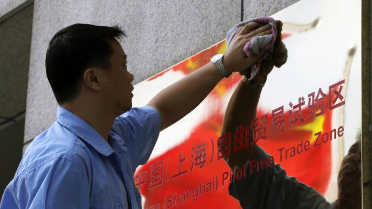 A reflection of the Chinese national flag is seen in a sign for the new China (Shanghai) Pilot Free Trade Zone, as a worker cleans it, in Shanghai