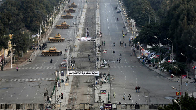 """Military tanks deployed in front of the presidential palace in Cairo, Egypt, Sunday, Dec. 16, 2012. Key Egyptian rights groups called Sunday for a repeat of the first round of the constitutional referendum, alleging the vote was marred by widespread violations. Islamists who back the disputed charter claimed they were in the lead with a majority of """"yes"""" votes. (AP Photo/Hassan Ammar)"""