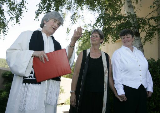 File - In this June 20, 2008 file photo, the Reverend Dr. Jane Spahr, left, a Presbyterian minister, performs a same-sex marriage for Sherrie Holmes, center, and Sara Taylor, at the Marin Civic Center in San Rafael, Calif. A Roman Catholic church in San Francisco that canceled a series of pre-Christmas services featuring gay ministers from other denominations is being criticized for sending a negative message to its predominantly gay and lesbian congregation. Pastor Steve Meriwether of Most Holy Redeemer Church late last month rescinded the invitations he had extended to Spahr and two other ministers at the direction of San Francisco Archbishop George Niederauer, the San Francisco Chronicle reported Friday, Dec. 23, 2011. (AP Photo/Eric Risberg, File)