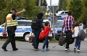 A German policeman directs migrants towards a registration …