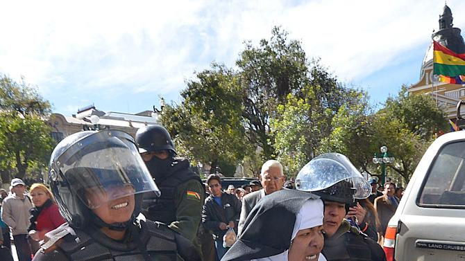 Riot policemen carry an activist dressed as a nun at Murillo square in La Paz