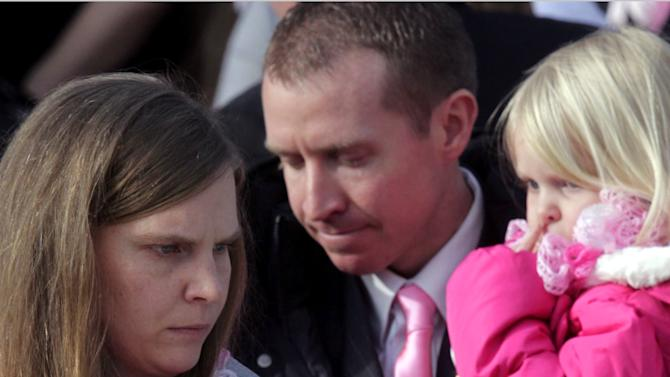 FILE-- in this photo taken on Dec. 22, 2012, Alissa Parker and her husband, Robbie carry their daughters, Samantha, 3, left, and Madeline, 4, following funeral services for their 6-year old daughter, Emilie, in Ogden, Utah. The moment Alissa Parker learned of a shooting at her daughter's school in Newtown, Conn., she suddenly regretted not pointing out what she had seen as security gaps at Sandy Hook Elementary School. Parker, whose daughter, Emilie, was among 20 first-graders killed in the Dec. 14 massacre, had thought security could have been tighter, although she never could have guessed it would be tested by a gunman with a military-style, semi-automatic rifle. (AP Photo/Rick Bowmer)