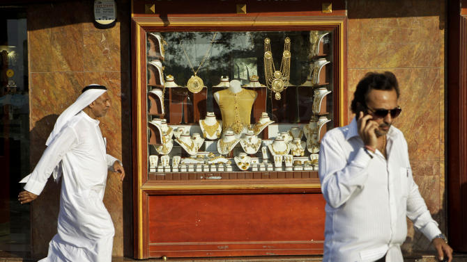 """In this Thursday Oct. 11, 2012 photo, an Emirati man passes by a jewelry shop in the gold suq in Dubai, United Arab Emirates. Dubai is sometimes called the """"City of Gold"""" because of its stunning growth from a sleepy Gulf port to a world-famous business crossroads in the space of a single generation. (AP Photo/Kamran Jebreili)"""