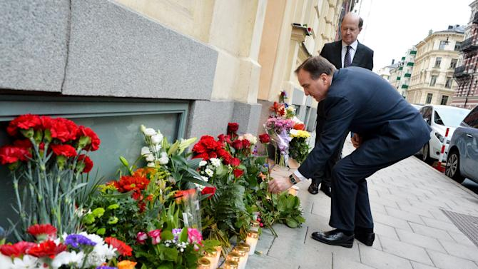 Sweden's Prime Minister Stefan Lofven leaves a red rose outside France embassy in in commemoration of the victims of the Paris attacks, in Stockholm, Sweden