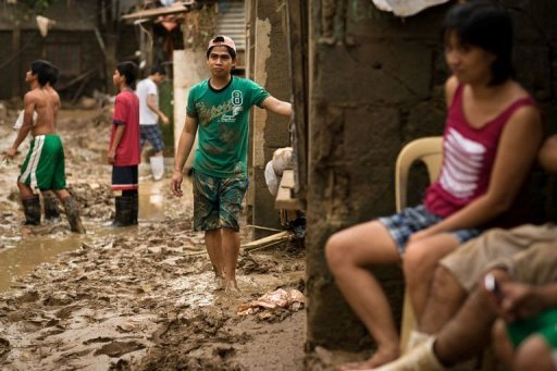 Local residents return to their homes and start to clean up their area from the mud left by the floods at a slum next to a river in San Mateo town, Rizal province. Emergency relief officials and doctors deployed to flood devastated communities in the Philippines Sunday to prevent outbreaks of disease as the death toll jumped to 85