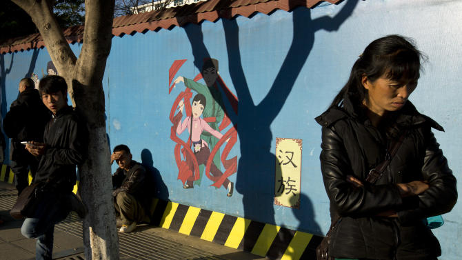 In this Monday, March 3, 2014 photo, people stand on a street near a wall painted with figures representing Han Chinese, center, and other ethnic groups living in the city as part of a tourism advertisement outside the Kunming Train Station in Kunming, in western China's Yunnan province. China said the vicious slashing spree Saturday that killed 29 people in the southern city was the work of separatists linked to international terrorism, but the assailants' homespun methods and low-tech weapons - nothing more than long knives - have led some analysts to suspect they didn't get outside help. (AP Photo/Alexander F. Yuan)