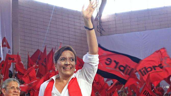 In this June 16, 2013 photo, presidential candidate Xiomara Castro, wife of ousted President Manuel Zelaya, waves to her supporters at the Free Party's convention in Tegucigalpa, Honduras. Polls show Castro, 53, leading seven other candidates ahead of the Nov. 24 election, including the military general who conducted the coup against Zelaya in June 2009. (AP Photo/Alberto Arce)
